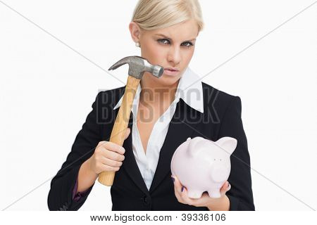 Stern businesswoman holding a hammer and a piggy-bank against white background