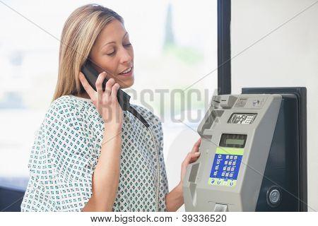 Female patient using payphone in hospital corridor