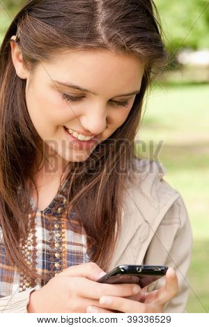 Close-up of a cute teenager using a smartphone in a park