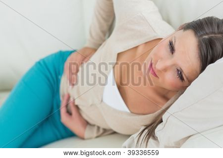 Woman lying on sofa looking sick in the living room