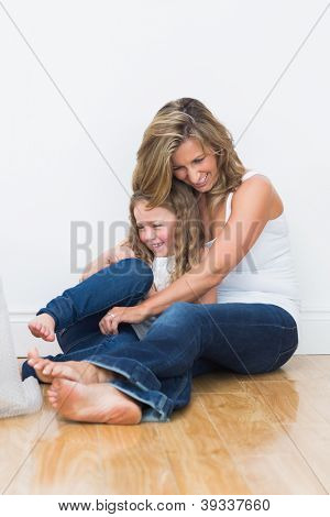 Laughing mother tickling her daughter on the floor