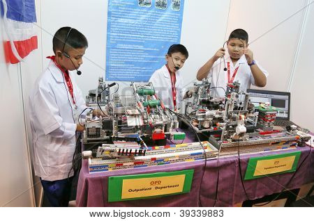 SUBANG JAYA - NOVEMBER 10:Unidentified students from Thailand demonstrates how robots dispense pills and medication at the World Robot Olympaid on November 10, 2012 in Subang Jaya, Malaysia.