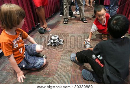 SUBANG JAYA - NOV 10: Unidentified visitors interact by playing with robots at the World Robot Olympaid on November 10, 2012 in Subang Jaya, Malaysia. This year's theme is Robots connecting people.