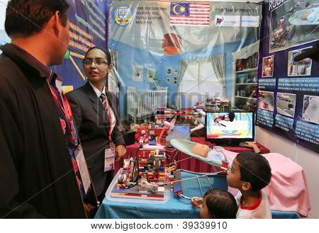SUBANG JAYA - NOVEMBER 10: A Malaysian inventor explains to visitors how the Nanny robot works taking care of an infant at the World Robot Olympaid on November 10, 2012 in Subang Jaya, Malaysia.