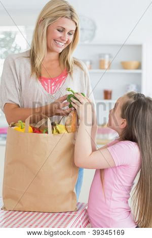 Woman giving green pepper to daughter from grocery bag in the kitchen