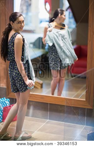 Woman holding up clothes and looking in the mirror in clothes store