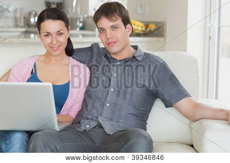 Young couple sitting on the couch in the living room while using the laptop