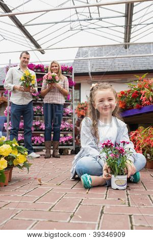 Happy family holding flower pots with little girl sitting on ground in garden centre