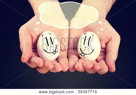male hand holding holding eggs with smiley faces, copyspace over their head