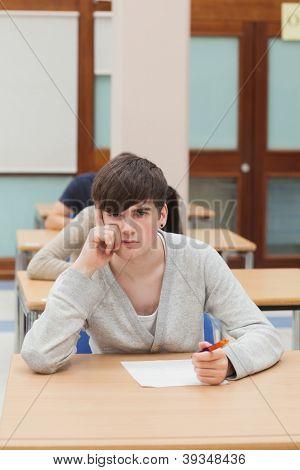 Man thinking during exam in exam hall