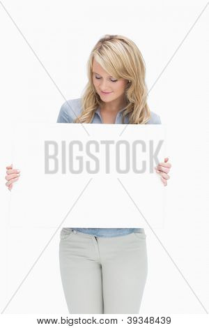 Woman looking at a large piece of paper while holding it
