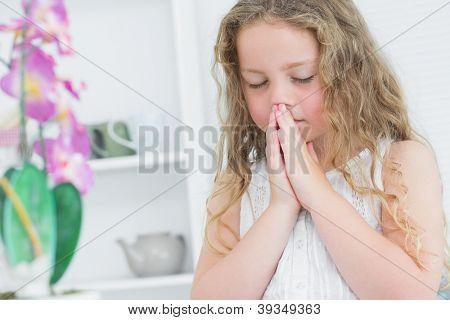 Girl with her close eyes praying about something