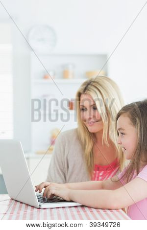 Mother and little girl sitting at the kitchen smiling with laptop