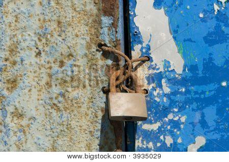 Old And Wet Iron Door With Padlock
