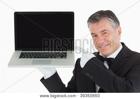 Smiling waiter pointing us something on a laptop in front of camera