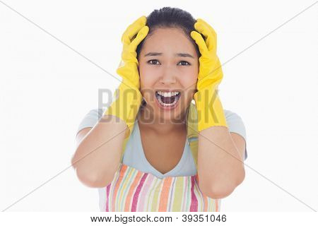 Distressed woman with hands on her head wearing apron and rubber gloves and screaming