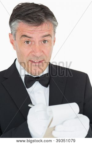 Surprised waiter in suit writing something into his notebook