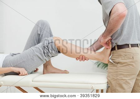 Close-up of a physiotherapist stretching the foot of a patient in a room