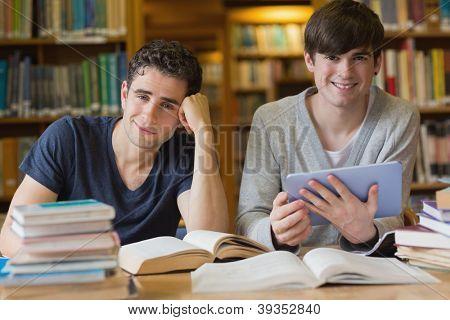 Jovens olhando para cima de estudar na biblioteca de usando um tablet pc