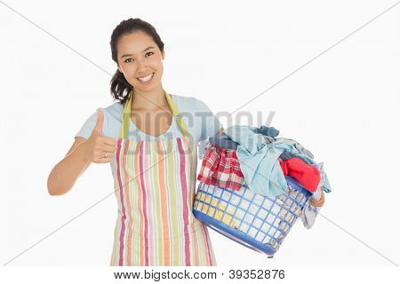 Smiling woman in apron carrying laundry basket and giving thumbs up