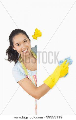 Mujer sonriente en el delantal y caucho guantes limpieza superficie blanca
