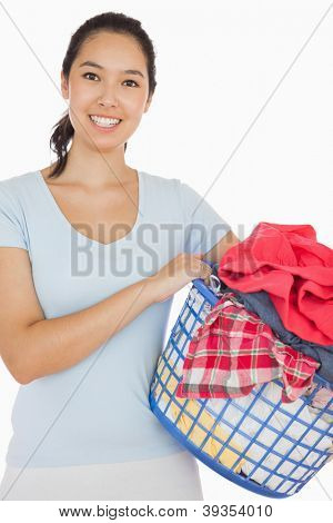 Smiling woman holding a basket full of laundry on a white background