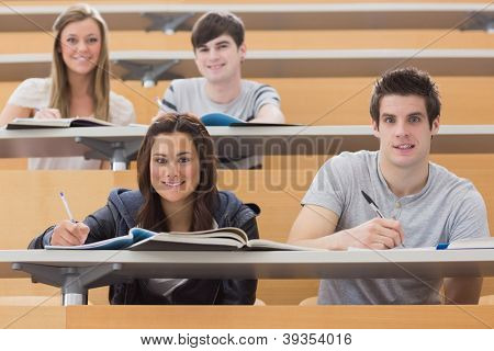 Students sitting at the desk while smiling at the lecture hall