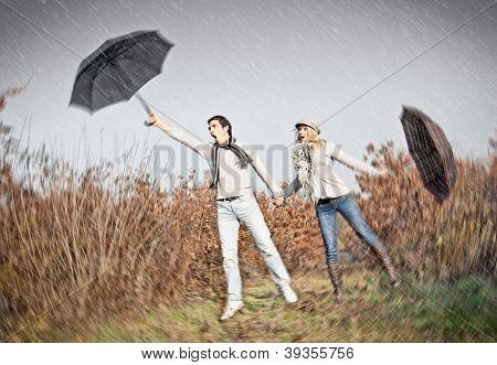 Frau und Mann mit Sonnenschirmen während starker Sturm-wind