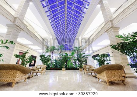 MOSCOW - DECEMBER 15: Hall with palms and wicker chairs in Crocus City Mall on December 15, 2011 in Moscow, Russia. Shopping center comprises 200 boutiques restaurants and cafes.