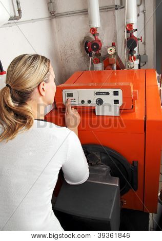 Woman Adjusting The Heating In The Boiler Room