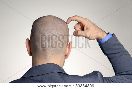 Rear view from a bald head man,thinking and touching his head.