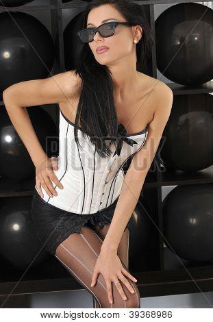 Attractive brunette wears white lingerie corset