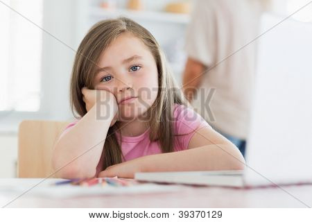 Child sitting while looking bored at the table at the kitchen with laptop pencils and paper