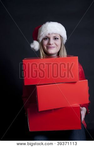 Cute Girl With Stack Of Blank Red Boxes And Santa Hat