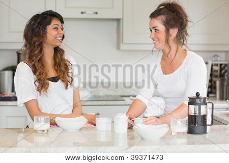 Two friends enjoying breakfast together in kitchen