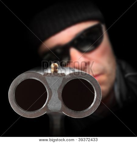 Gangster with shotgun aimed at you. Gun control concept. Close up with shallow DOF.