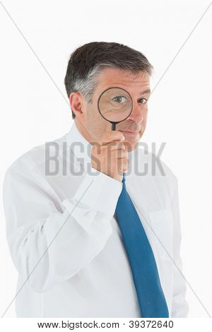 Inquisitive businessman looking through magnifying glass