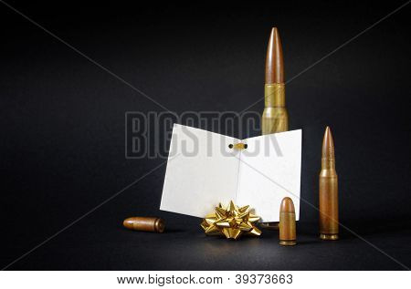 Composition with several gun bullets with a blank dedication card as an ironic gift