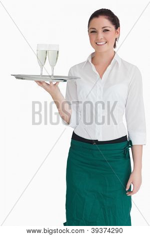 Smiling woman in suit holding a silver tray with glasses of champagne