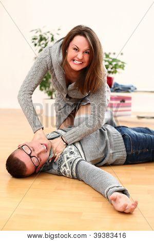 Angry woman choking a dead man lying on a floor