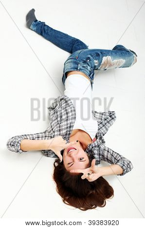 Attractive woman making frame with her hands lying on a white floor