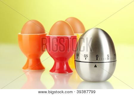 egg timer and egg in color stand on green background
