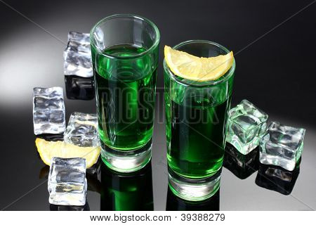 Two glasses of absinthe, lemon and ice on grey background