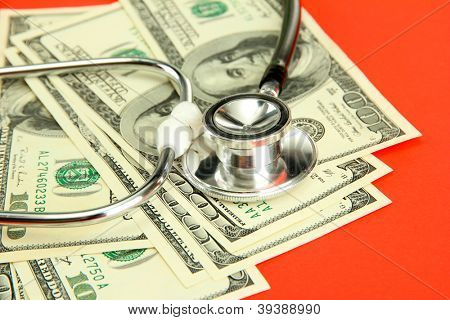 Healthcare cost concept: stethoscope and dollars on red background