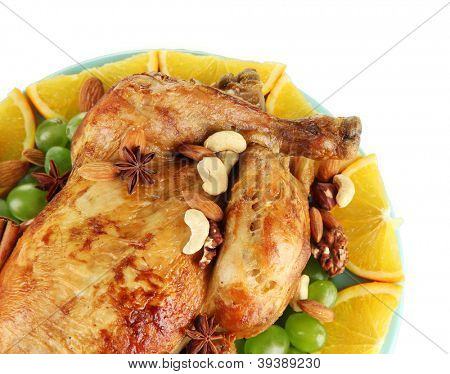 whole roasted chicken with grapes, oranges and spices on blue plate on white background close-up