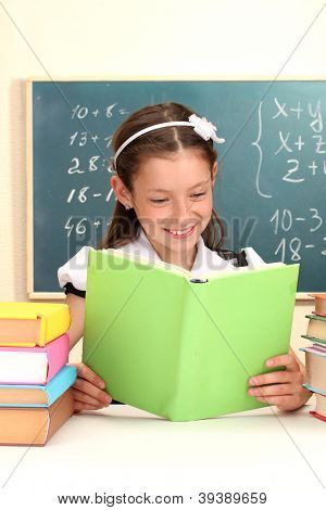 beautiful little schoolgirl in classroom reading the book