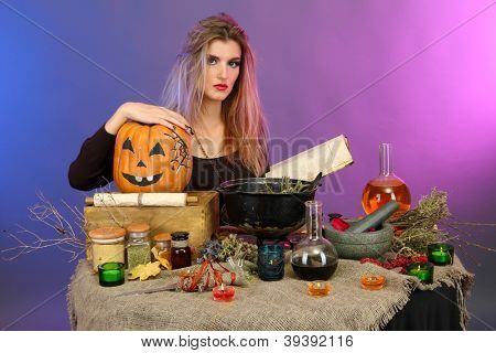 Halloween witch preparing poison soup in her cauldron on color background