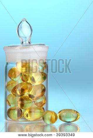 Capsules in receptacle on blue background