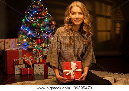 young smiling woman holding red christmas gift