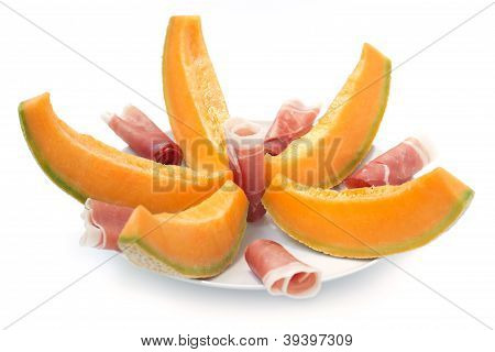 plate of sliced ham and melon